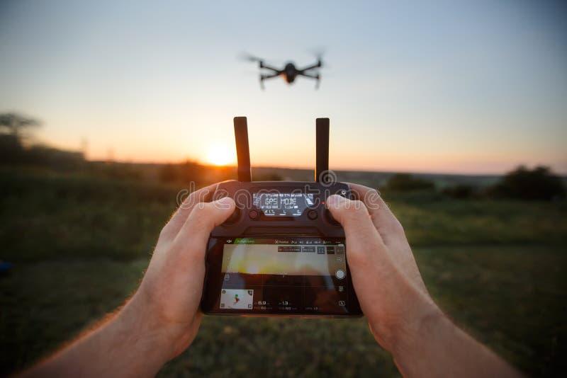 Точка зрения сняла человека держа удаленный регулятор с его руками и принимая воздушное видео фото Quadcopter летает стоковая фотография
