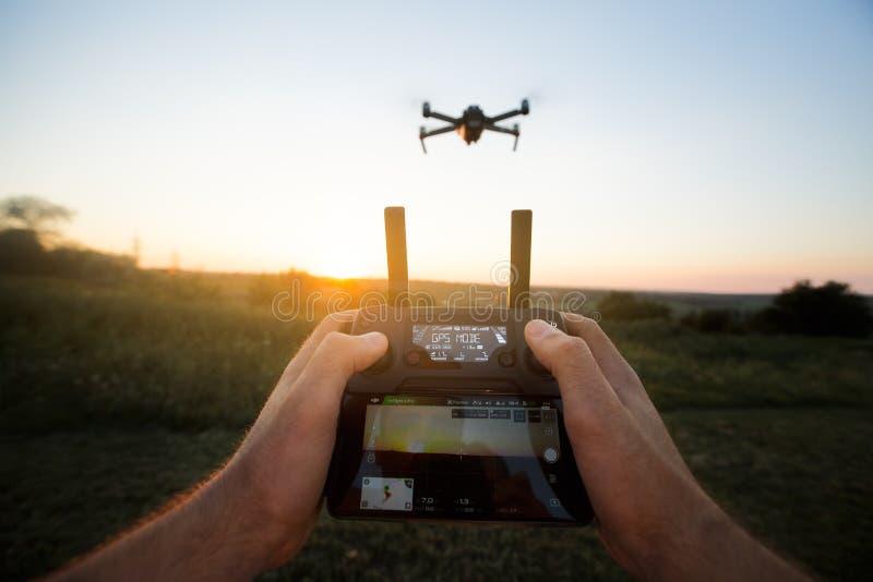 Точка зрения сняла человека держа удаленный регулятор с его руками и принимая воздушное видео фото Quadcopter летает стоковое изображение