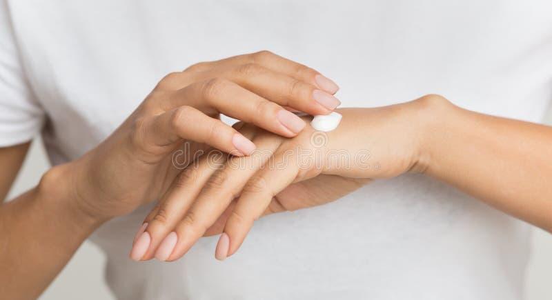 Точка сливк Женщина прикладывая moisturizing лосьон руки стоковое изображение