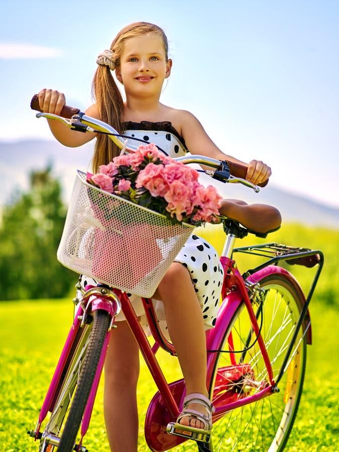 Точки польки девушки ребенка нося белые одевают езды bicycle в парк стоковые изображения rf