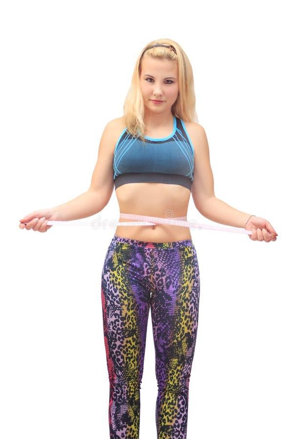 Тощая sporty девушка измеряя ее талию стоковая фотография rf