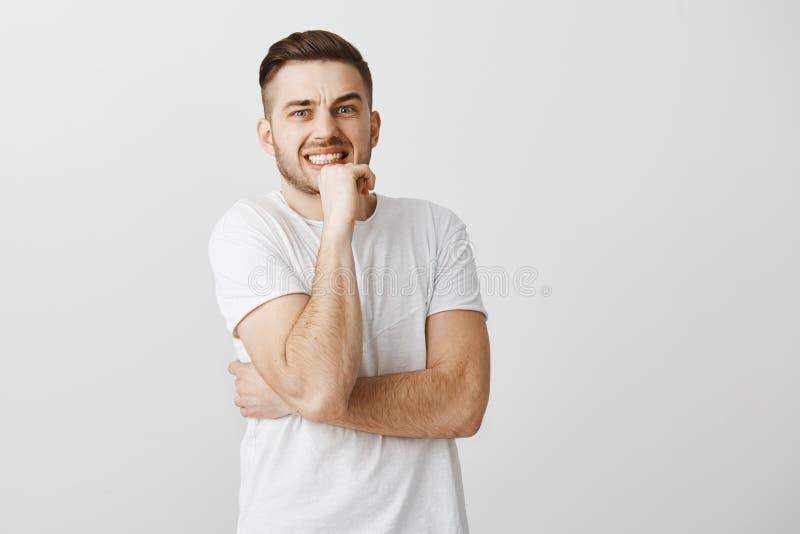 То было тягостно Потревоженное стильное и красивое молодое европейское небритое мужское брюнет в белой футболке обхватывая зубы стоковые изображения rf