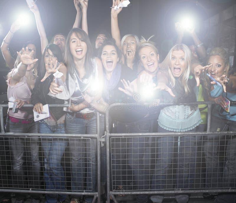 Толпа молодых женских вентиляторов кричащих и веселя на концерте стоковые фотографии rf