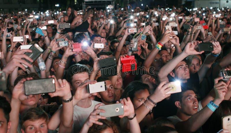 Толпа людей принимая фото с телефоном стоковое изображение rf