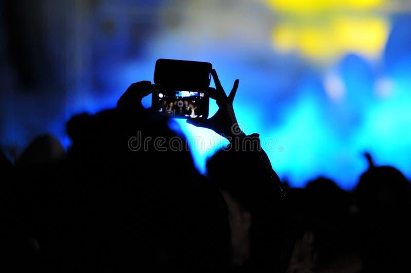 Толпа людей принимая фото с smartphones на концерт стоковая фотография rf