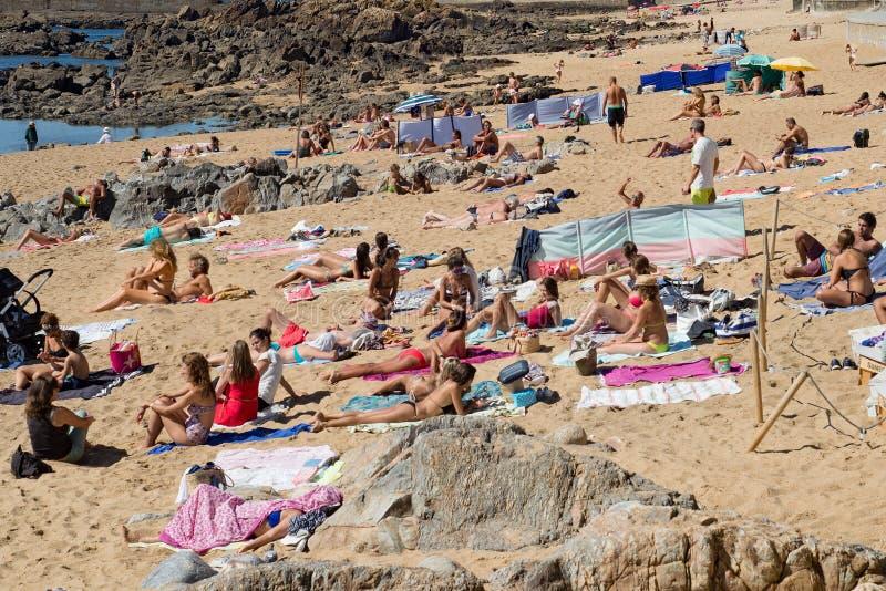 Толпить скалистый пляж в Порту, Португалии Люди загорая на песке стоковая фотография rf
