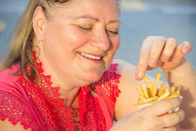 Толстая женщина есть фраи гамбургера и француза фаст-фуда в caf стоковые изображения rf