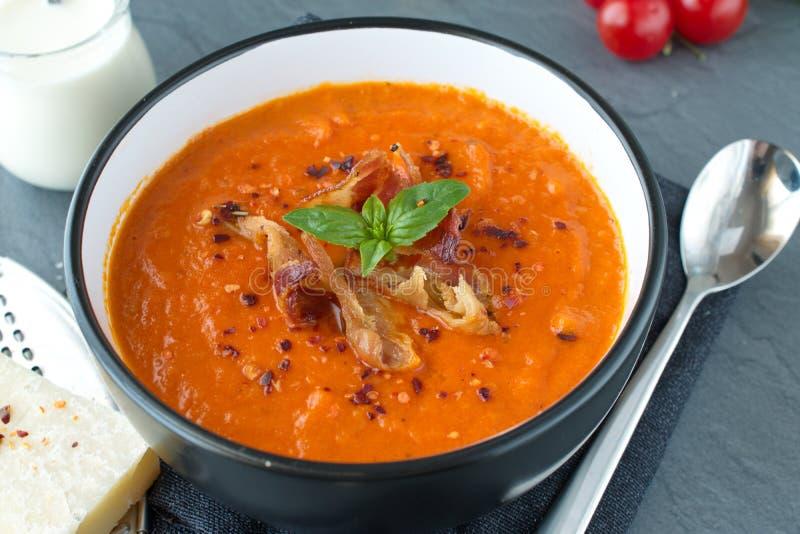 Толстый суп томата с базиликом и зажаренный бекон в черном керамическом шаре на серой абстрактной предпосылке еда здоровая стоковые фотографии rf