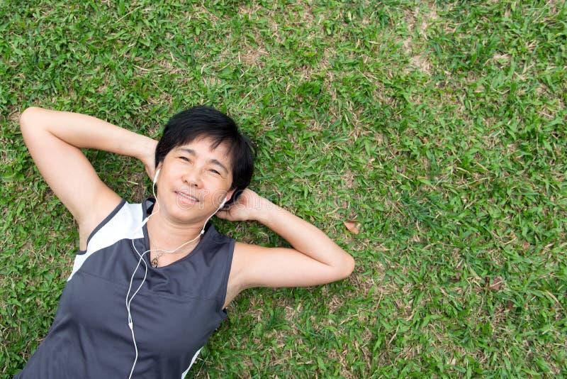 трава кладя старшую женщину стоковая фотография rf