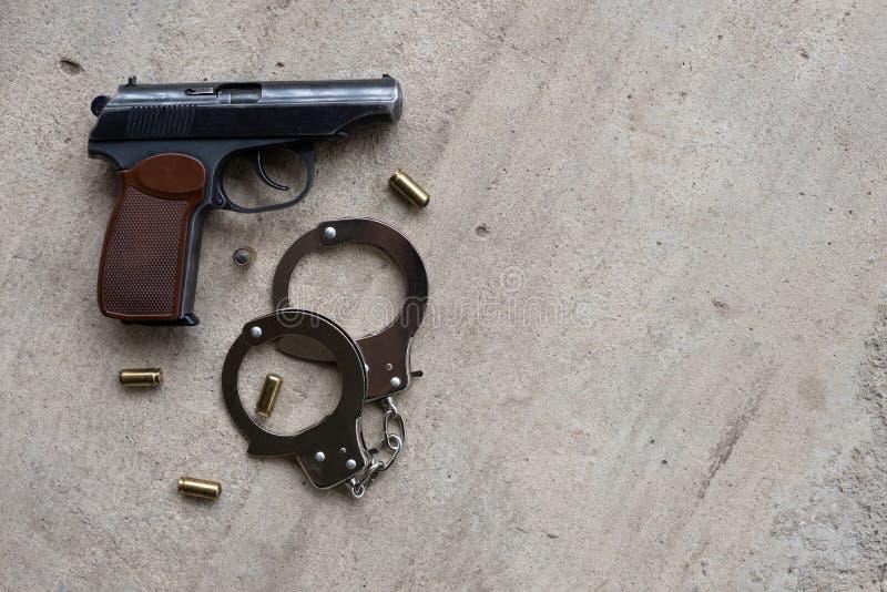 Травматичное оружие металла для самозащиты с пулями 9 mm и наручники на серой конкретной предпосылке E стоковые фотографии rf