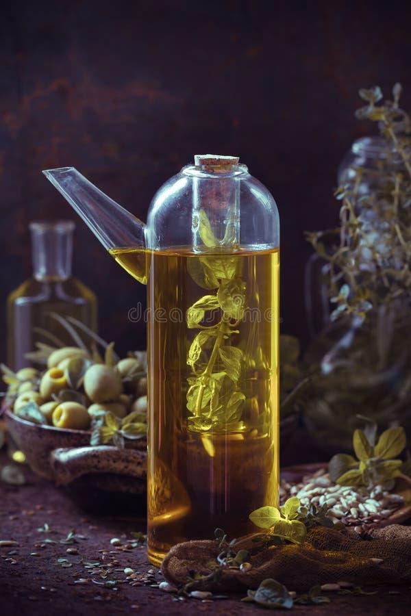 Травы ветвей плодов оливкового масла бутылки стоковые фотографии rf