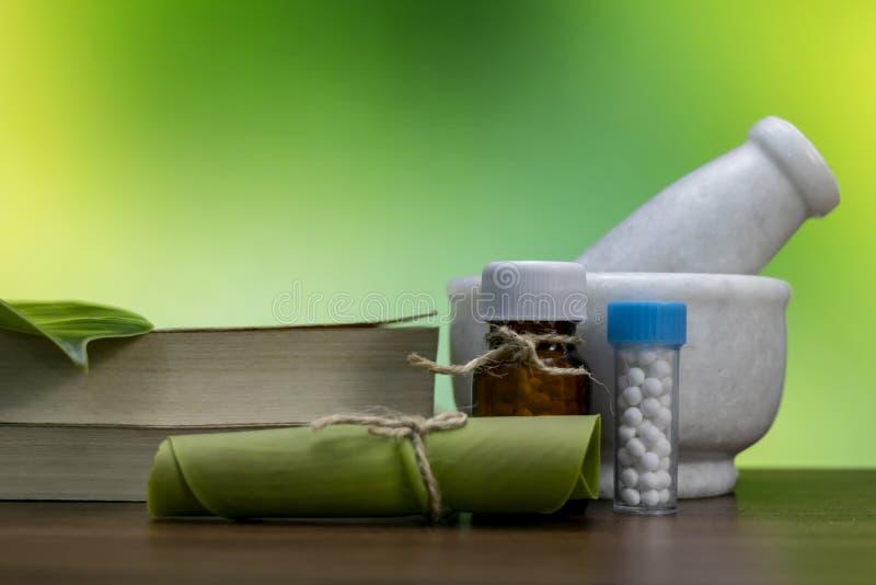 Травы лечения и миномет, книга, белые бутылки глобулы, и свернутые лист на деревянной поверхности с зеленой желтой предпосылкой А стоковые изображения rf