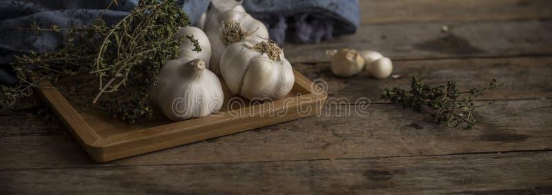 Травы чеснока и кухни на деревянном столе стоковое изображение