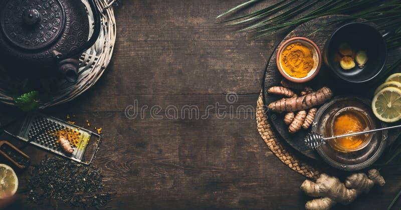 Травяная предпосылка чая турмерина Чашка здорового чая специи турмерина с чайником и ингредиентами утюга: лимон, имбирь, ручки ци стоковое изображение rf