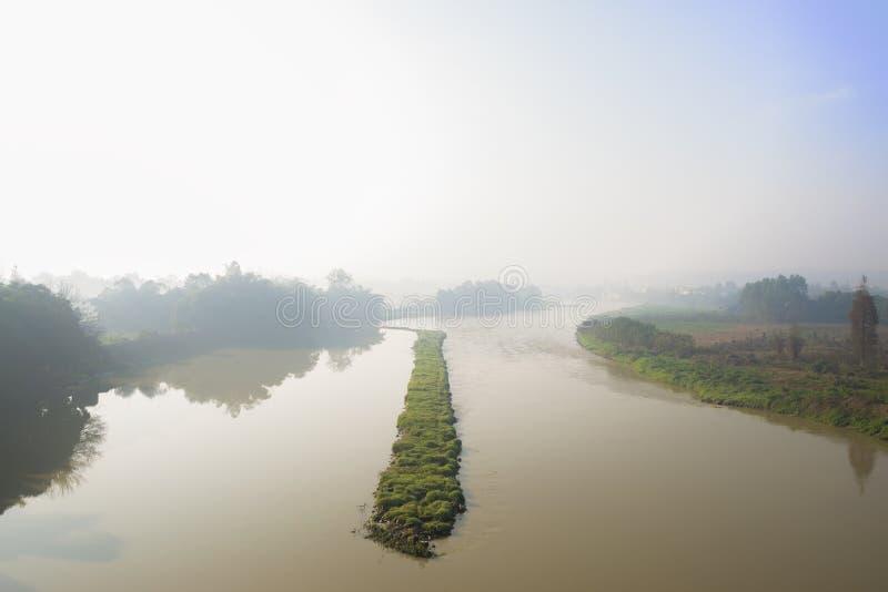 Травянистый dike диверсии в реке солнечного туманного утра зимы стоковые изображения