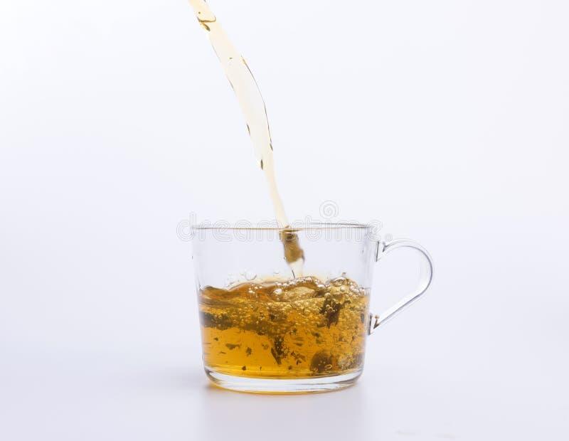 Травяной чай лить в чашке изолированной на белизне стоковые фото