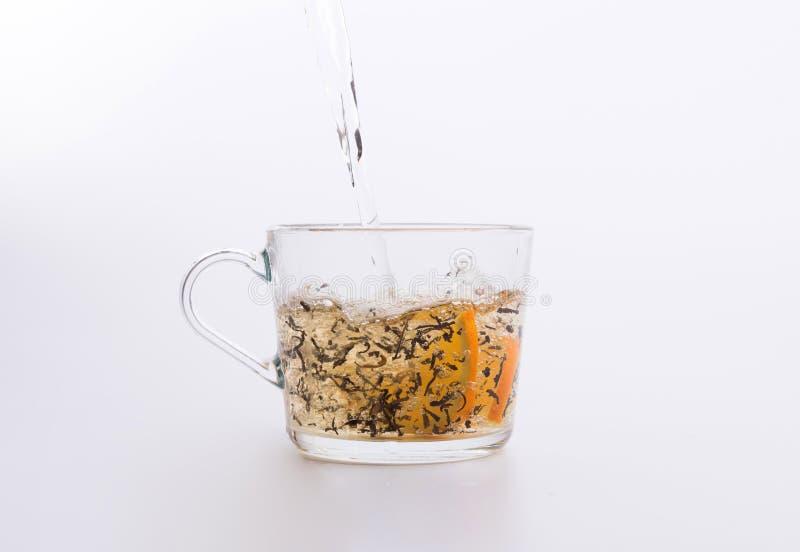Травяной чай лить в чашке изолированной на белизне стоковая фотография