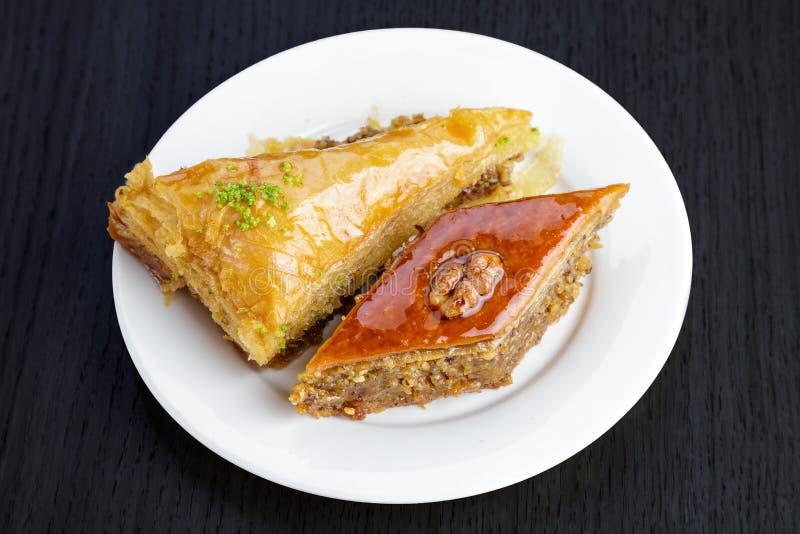 Традиционная арабская бахлава десерта с грецкими орехами и кардамоном, на деревянном столе Домодельная бахлава с гайками и медом стоковое изображение
