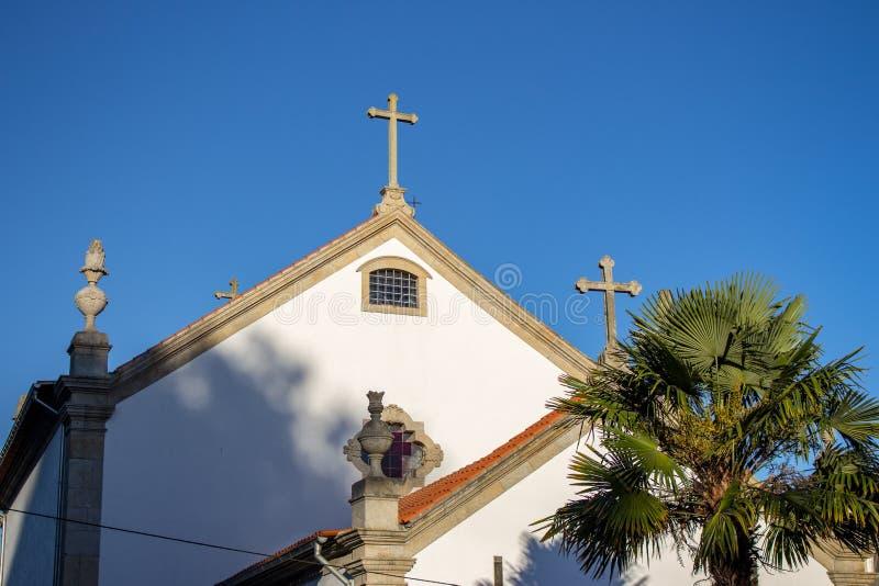 Традиционная белая португальская церковь с пальмой в утре Среднеземноморской религиозный ориентир Католическая башня с крестом стоковые изображения