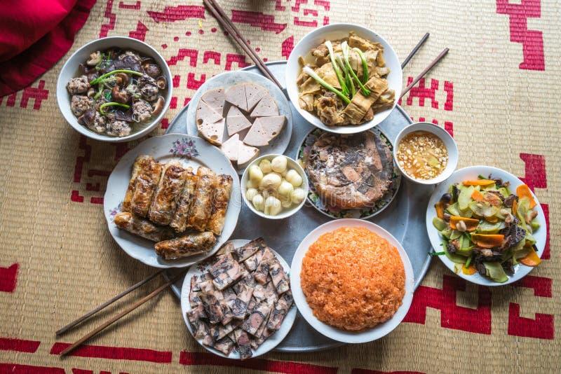 Традиционная въетнамская еда на лунный праздник Tet Нового Года весной, помещенная на новой зацветенной циновке осоки, на последн стоковые фото