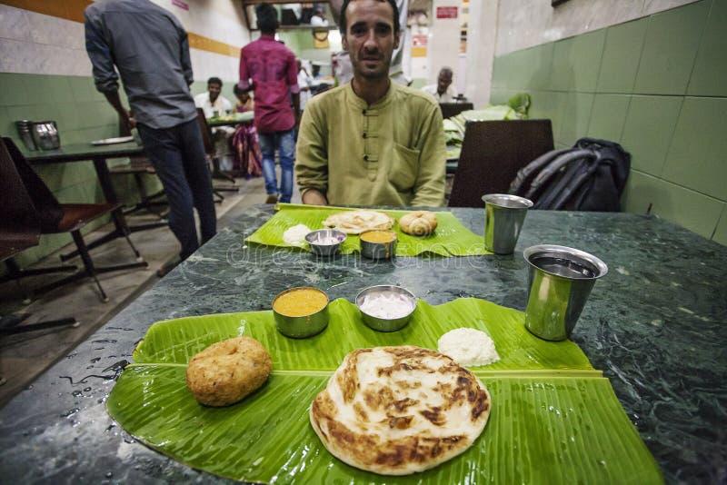 Традиционная индийская еда обеда служила на зеленых лист кокоса стоковые изображения