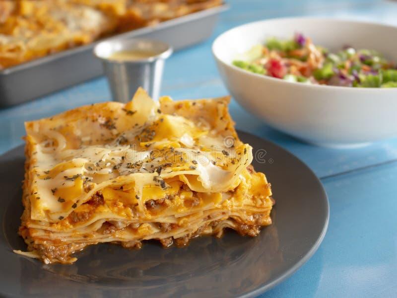 Традиционная плита макаронных изделий лазаньи с сыром сливк томатного соуса базилика белыми и говяжим фаршем и салатом стоковые фото