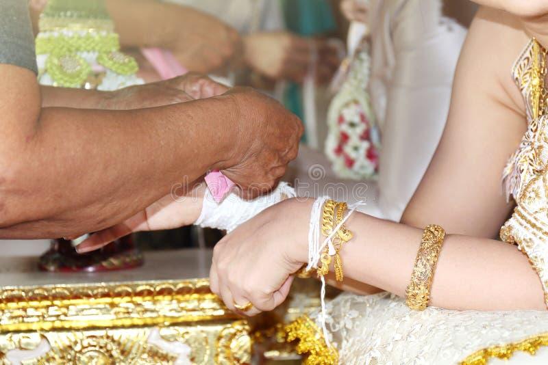 Традиционная тайская свадьба, руки невесты связана с потоком от более старой культуры свадебной церемонии традиции в Таиланде стоковая фотография