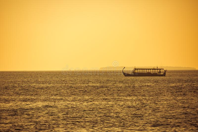 Традиционная шлюпка Dhoni Мальдивов в море захода солнца, золотых тонах и расслабляющей тропической погоде стоковое фото