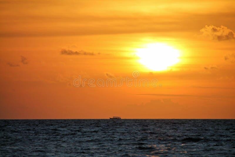 Традиционная шлюпка Dhoni на дистантном горизонте с оранжевым заходом солнца в Мальдивах стоковые фото