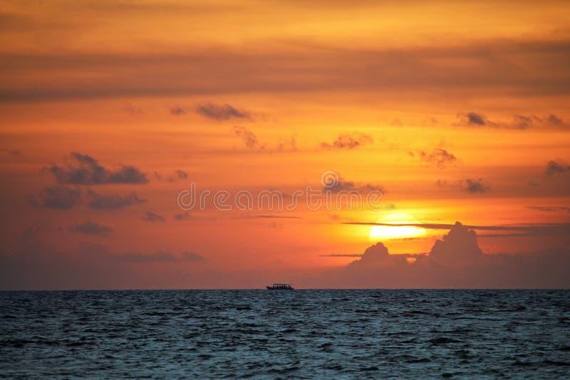 Традиционная шлюпка Dhoni на дистантном горизонте с оранжевым заходом солнца в Мальдивах стоковое фото rf