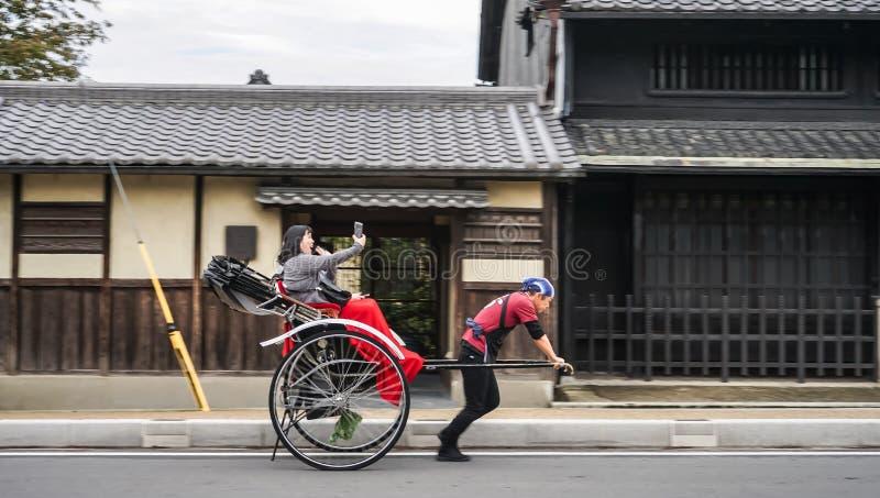 Традиционная японская рука тележки вытянула рикшу в Nara при жизнерадостные туристы принимая selfi фото на телефоне стоковое фото