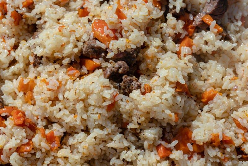 Традиционное азиатское кулинарное блюдо - pilaf Взгляд конца-вверх восточной вкусной предпосылки еды Ингредиенты: рис с кусками м стоковая фотография