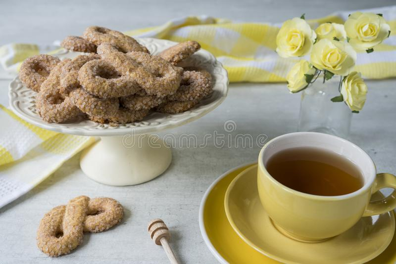 Традиционное печенье от Нидерланд вызвало Krakeling, на стойке белого торта желтая чашка чаю стоковая фотография