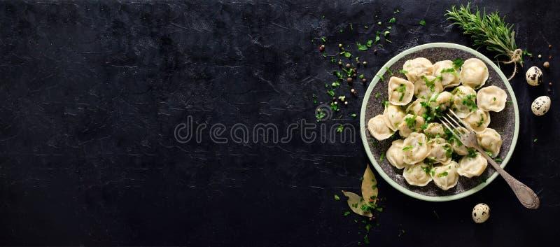 Традиционное русское pelmeni, равиоли, вареники с мясом на черной конкретной предпосылке Петрушка, яичка триперсток, перец стоковая фотография rf