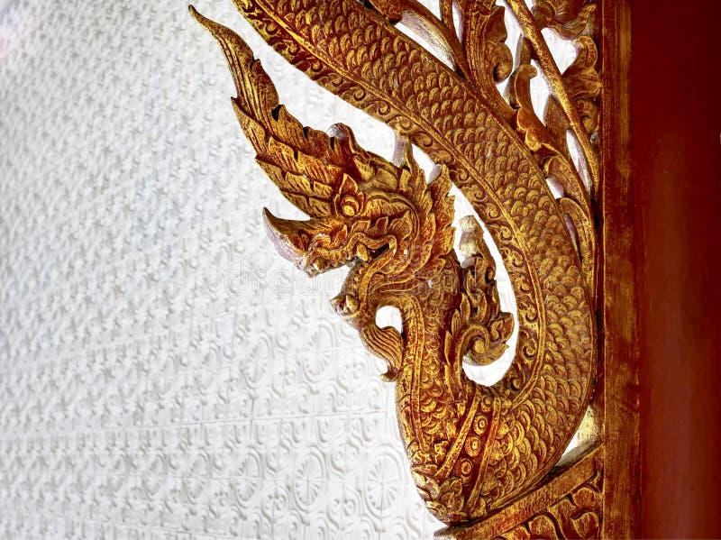 Традиционное тайское искусство высекая золотой Naga на виске стоковые изображения rf