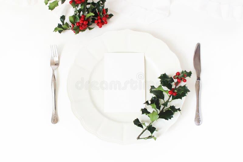 Традиционное урегулирование места таблицы рождества Серебряные столовый прибор, ветви ягоды падуба, плита фарфора и лента шелка у стоковые фото
