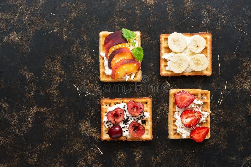 Традиционные бельгийские waffles с плодоовощами и ягодами, взгляд сверху Темная предпосылка, космос экземпляра Вафли с клубниками стоковая фотография rf