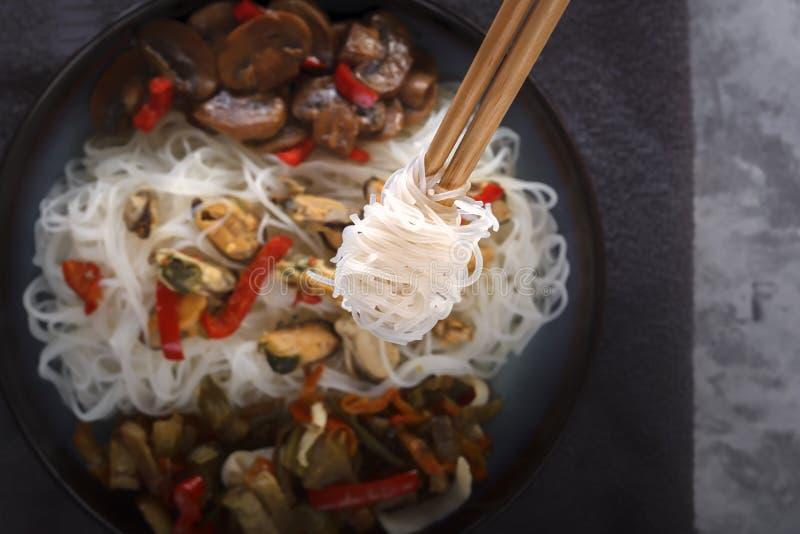 Традиционные деревянные палочки со спиральными лапшами риса на предпосылке блюда с морепродуктами, овощами и перцами стоковые фото