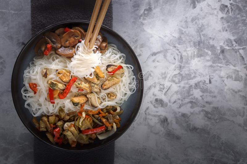 Традиционные деревянные палочки со спиральными лапшами риса на предпосылке блюда с морепродуктами, овощами и перцами стоковое фото rf