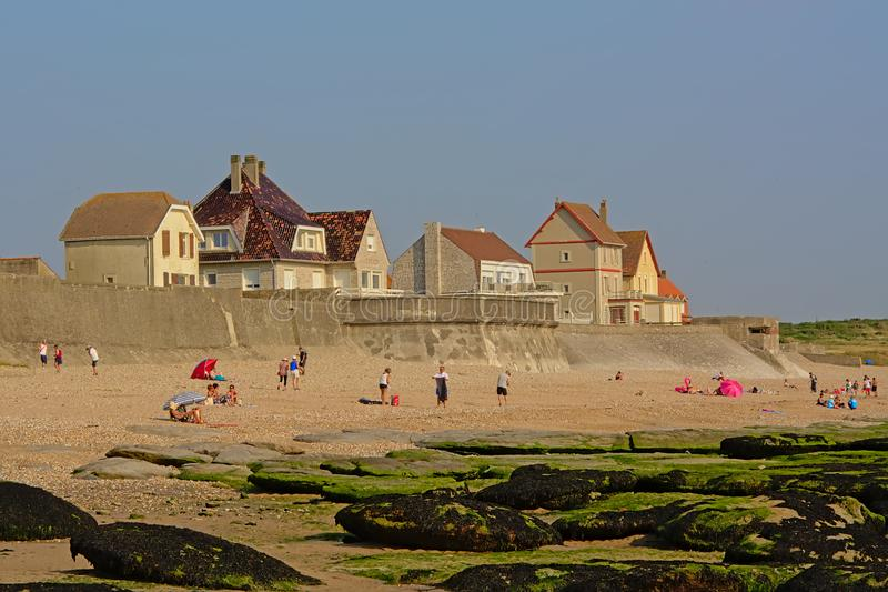 Традиционные дома на dike Северного моря в Audresselles, Франции, с пляжем с людьми и мшистым побережьем утеса в фронте стоковое изображение rf