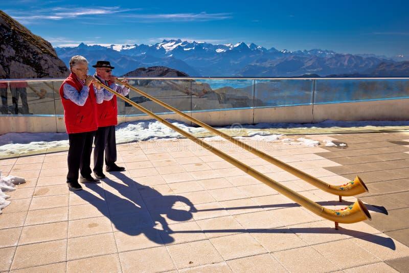 Традиционные игроки Alphorn швейцарца на горном пике Pilatus стоковая фотография