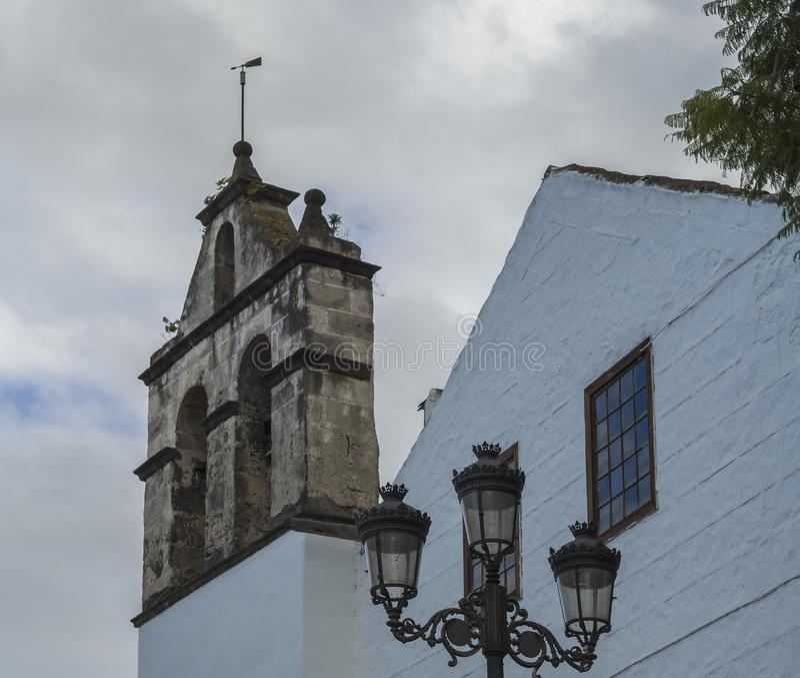Традиционные колокольня камня церков и уличный фонарь в Puerto de Ла cruz, Испании, Канарских островах, Тенерифе, голубом небе стоковое изображение