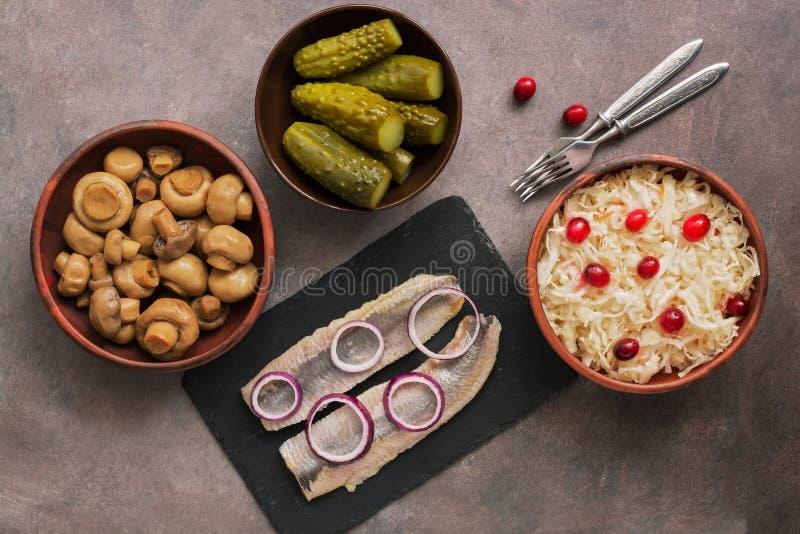 Традиционные русские закуски, sauerkraut с клюквами, соленьями, замаринованными грибами champignon, marinated сельдями : стоковое фото