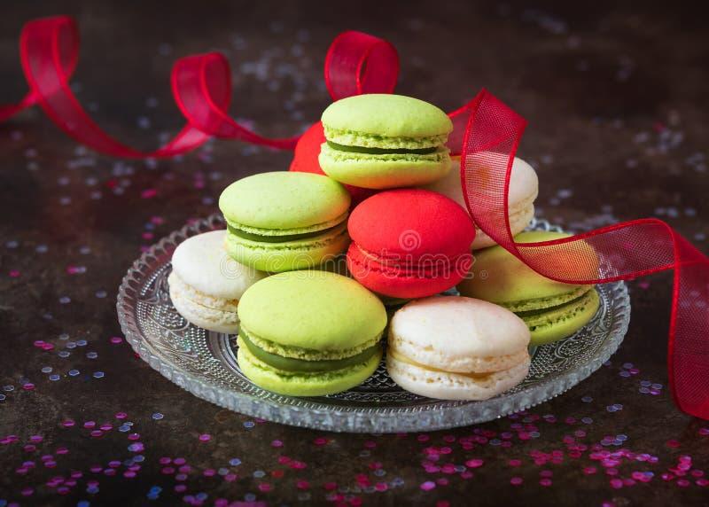 Традиционные французские красочные macarons в стеклянной пластинке на темной предпосылке с космосом экземпляра Красочные французс стоковые фотографии rf