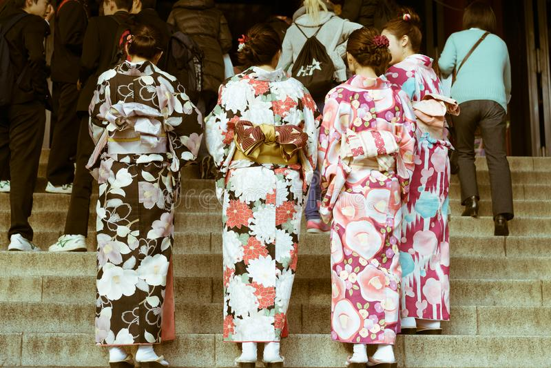 Традиционные японские женщины нося кимоно стоя на лестницах на виске Senso-ji, Asakusa, токио, Японии стоковые фото