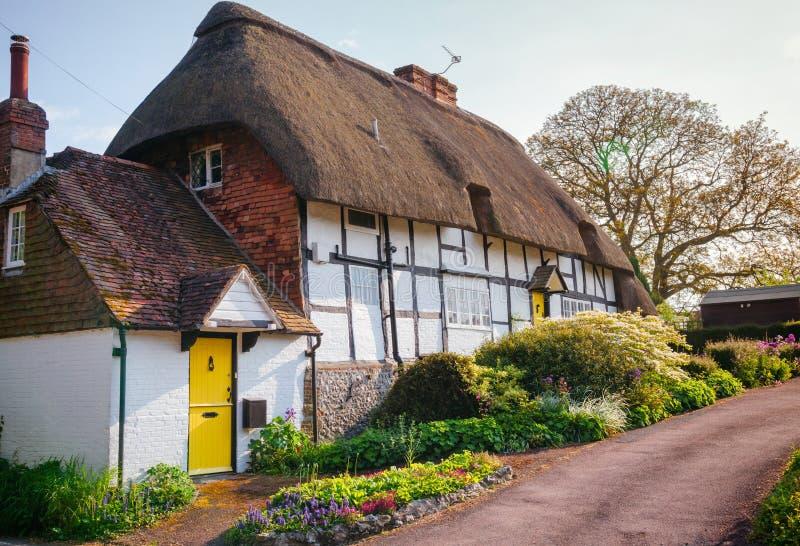 Традиционный английский покрыванный соломой дом с украшением цветка в Sou стоковые фото