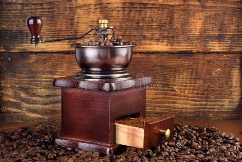 Традиционный деревянный точильщик мельницы кофе с зажаренными в духовке кофейными зернами и деревянной предпосылкой стоковые изображения rf