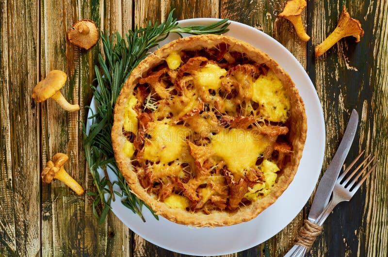Традиционный домодельный шведский пирог - киш при грибы, сыр и розмариновое масло лисички украшенные с винтажным kinife и вилкой стоковые изображения