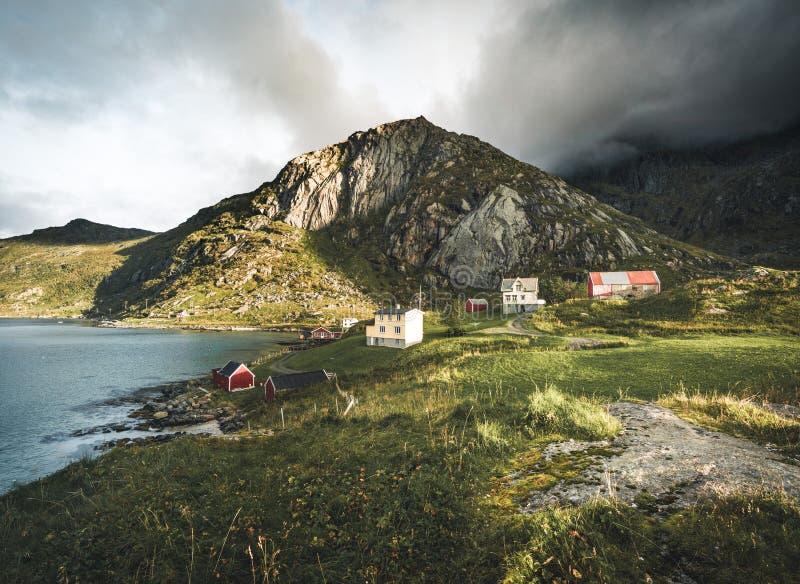 Традиционный красный дом fishin в Bjoernsand около Reine в Lofoten, Норвегии с красными домами rorbu После полудня захода солнца  стоковое фото rf