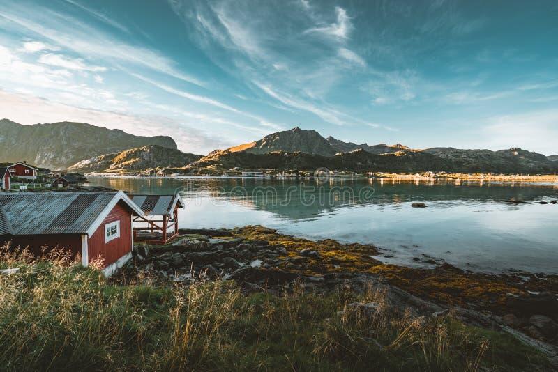 Традиционный красный дом fishin в Bjoernsand около Reine в Lofoten, Норвегии с красными домами rorbu После полудня захода солнца  стоковое изображение rf